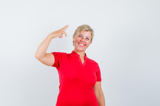 Rijpe vrouw die met hand en vingers in rood t-shirt gebaart en zelfverzekerd kijkt.