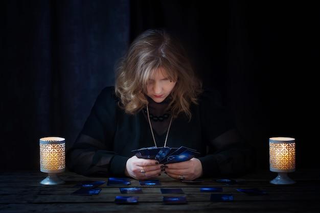 Rijpe vrouw die met kaarten op dark raadt