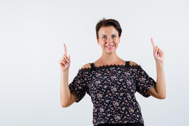 Rijpe vrouw die met wijsvingers in bloemenblouse, zwarte rok benadrukt en vrolijk kijkt. vooraanzicht.