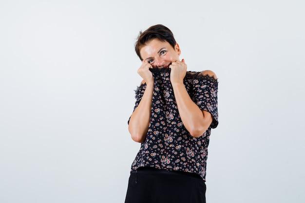 Rijpe vrouw die mond behandelt met blouse in blouse en leuk kijkt. vooraanzicht.