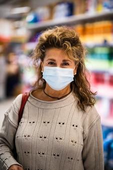 Rijpe vrouw die naar camera glimlacht terwijl het dragen van masker in supermarkt
