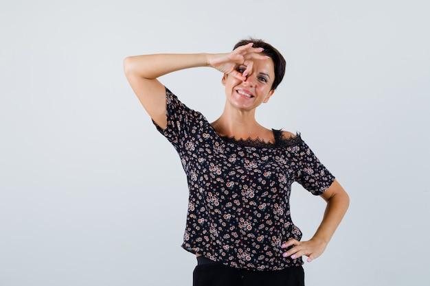 Rijpe vrouw die ok gebaar op oog toont terwijl handen op taille in blouse wordt gehouden en er schattig uitziet. vooraanzicht.