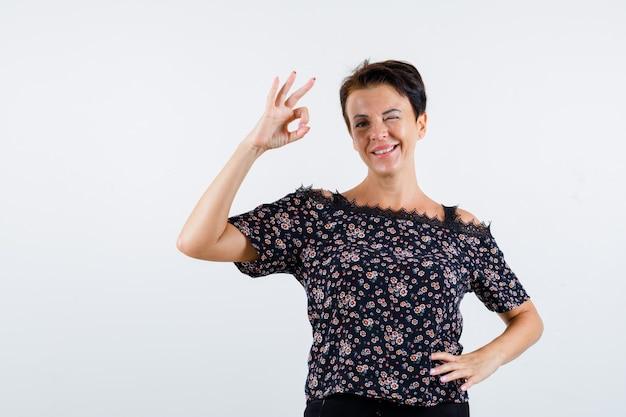 Rijpe vrouw die ok teken toont, hand op taille houdt, in bloemenblouse, zwarte rok knipoogt en vrolijk, vooraanzicht kijkt.