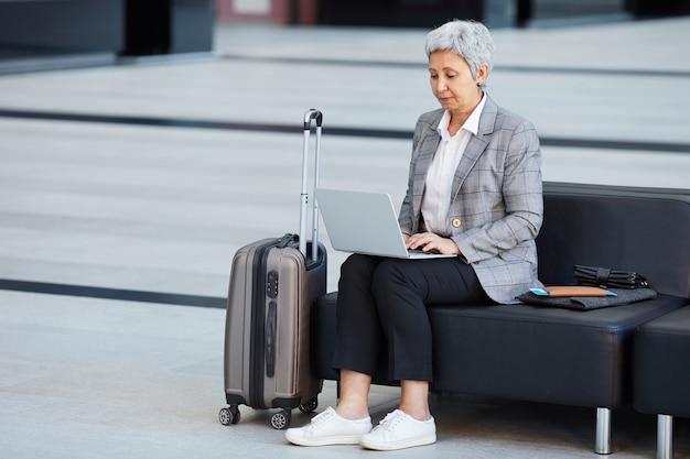 Rijpe vrouw die online op laptop zittend op bank in wachtkamer van de luchthaven werkt