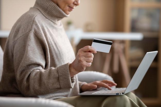 Rijpe vrouw die online winkelt