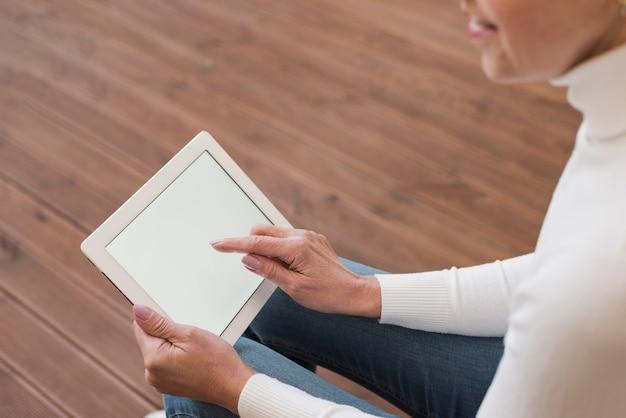 Rijpe vrouw die op haar tablet binnen kijkt