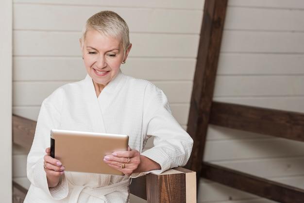 Rijpe vrouw die op haar tablet thuis kijkt