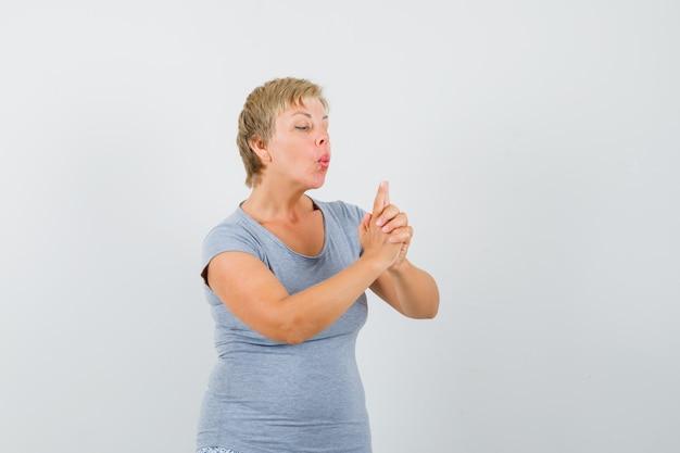 Rijpe vrouw die op vingerpistool in grijs t-shirt blaast en zelfverzekerd kijkt