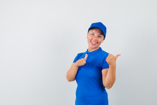 Rijpe vrouw die opzij met duimen omhoog in blauw t-shirt wijst en vrolijk kijkt.