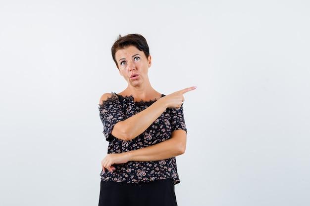 Rijpe vrouw die rechts met wijsvinger in bloemenblouse en zwarte rok richt en ernstig, vooraanzicht kijkt.
