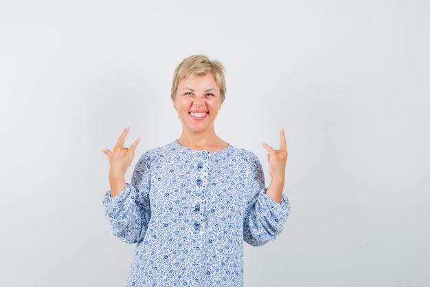 Rijpe vrouw die rock-'n-roll-gebaar in overhemd toont en gelukkig kijkt
