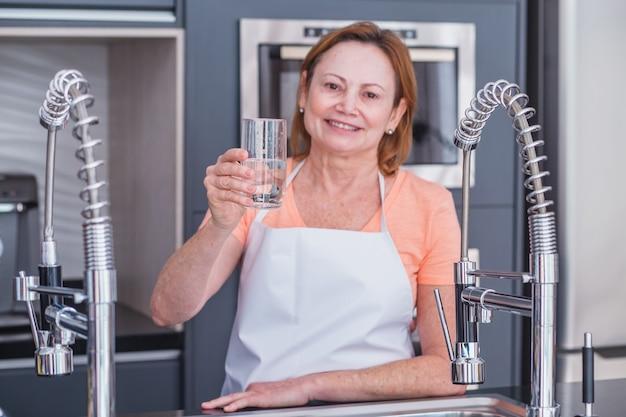 Rijpe vrouw die 's ochtends water drinkt in de keuken