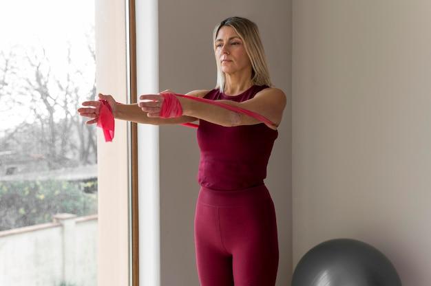 Rijpe vrouw die sportoefeningen doet naast haar raam
