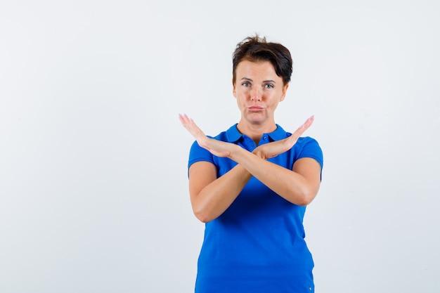 Rijpe vrouw die stopgebaar in blauw t-shirt toont en teleurgesteld kijkt. vooraanzicht.