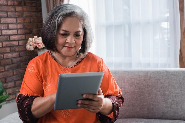 Rijpe vrouw die tabletcomputer met behulp van