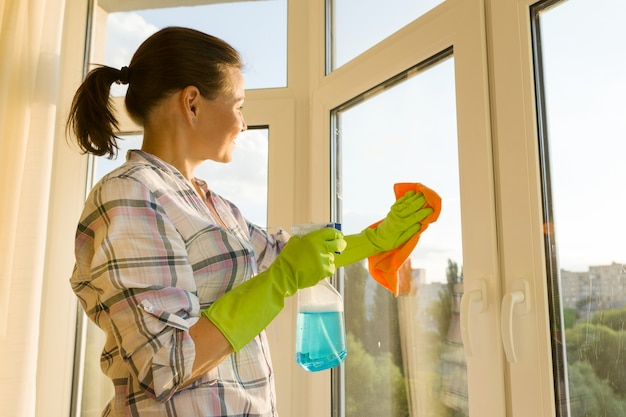 Rijpe vrouw die thuis het venster wast