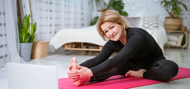 Rijpe vrouw die training op de mat doet