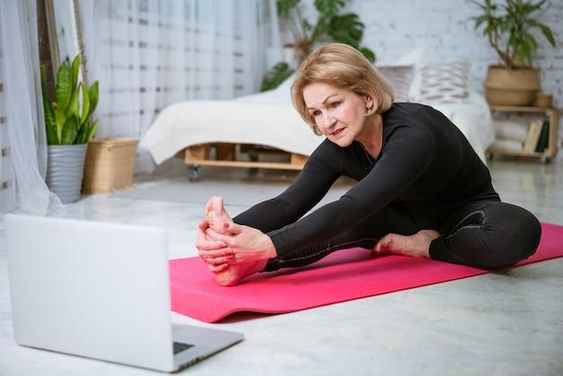 Rijpe vrouw die training op de mat online op laptop doet