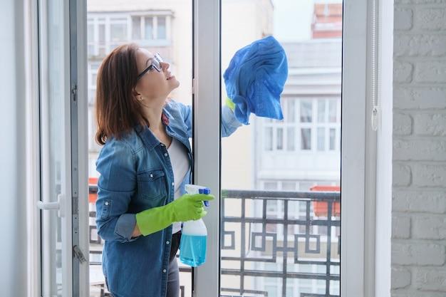 Rijpe vrouw die vensters thuis in het voorjaar schoonmaakt
