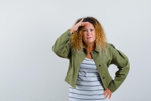 Rijpe vrouw die ver weg met hand boven hoofd in groen jasje, t-shirt kijkt en gericht, vooraanzicht kijkt.