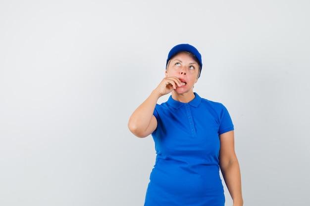 Rijpe vrouw die vingers in t-shirt bijt en verward kijkt