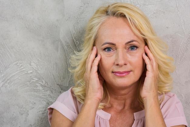 Rijpe vrouw die wat hoofdpijn heeft