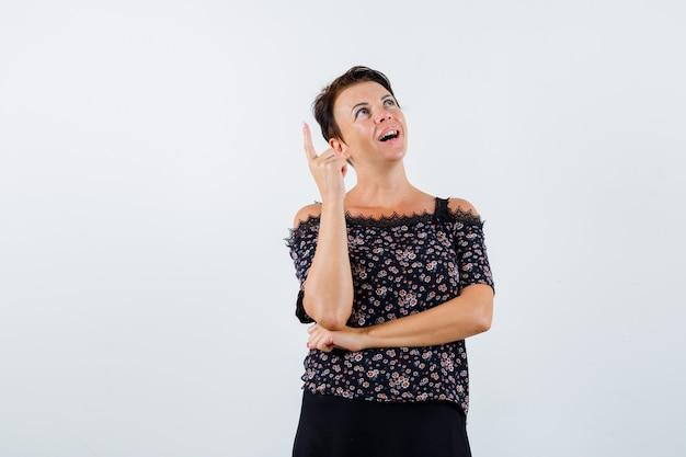 Rijpe vrouw die wijsvinger in eureka-gebaar opheft terwijl hand onder elleboog in bloemenblouse en zwarte rok wordt gehouden en verstandig kijkt. vooraanzicht.