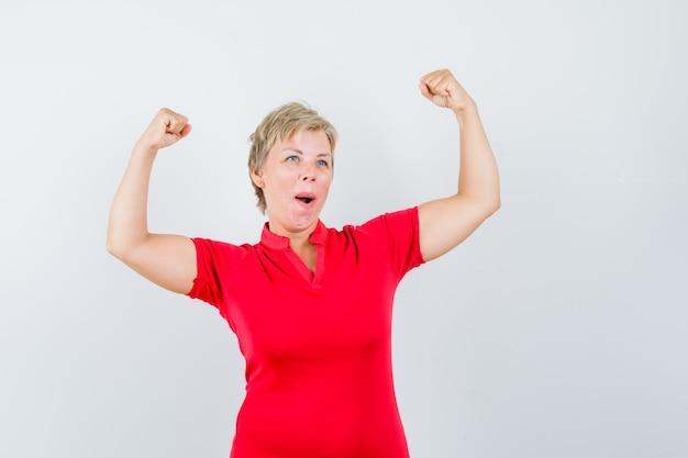 Rijpe vrouw die winnaargebaar in rood t-shirt toont en gelukkig kijkt
