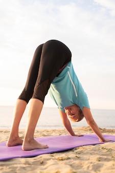 Rijpe vrouw die yoga op het strand doet