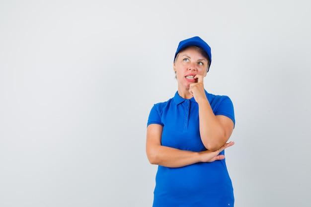 Rijpe vrouw die zich in denken stelt in blauw t-shirt en aarzelend kijkt