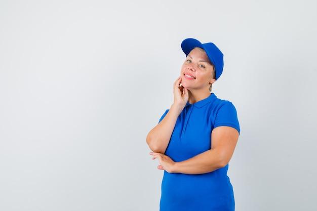Rijpe vrouw die zich in het denken bevindt stelt in blauw t-shirt en positief kijkt