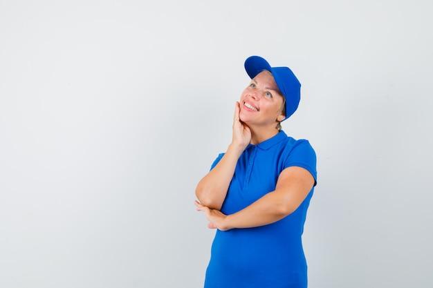 Rijpe vrouw die zich in het denken bevindt stelt in blauw t-shirt en vrolijk kijkt.