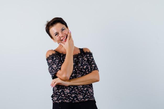 Rijpe vrouw die zich in het denken stelt stelt terwijl het glimlachen in blouse en aantrekkelijk kijkt. vooraanzicht.