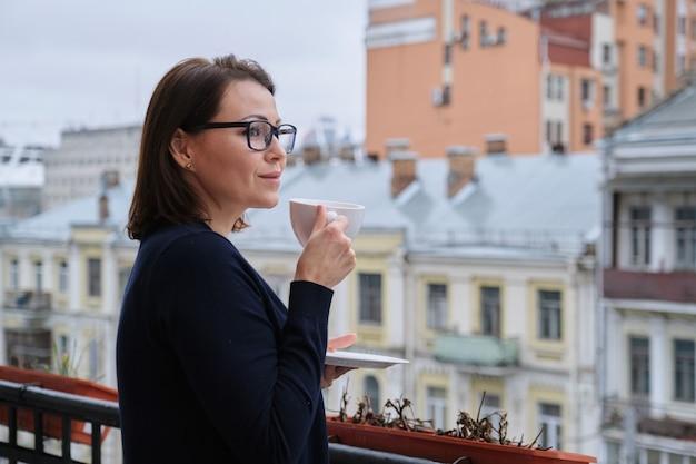 Rijpe vrouw die zich op open balkon met kop thee bevindt