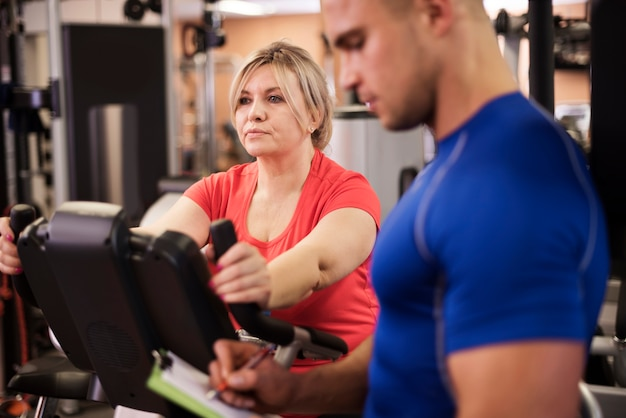 Rijpe vrouw doet oefenen met trainer