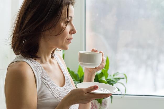 Rijpe vrouw drinkt koffie in de ochtend en kijkt uit het raam