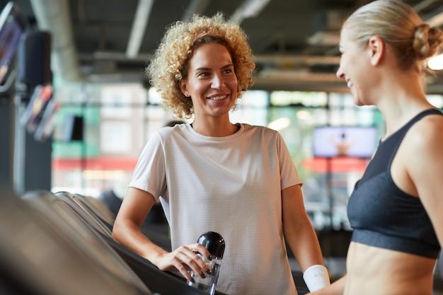 Rijpe vrouw drinkwater glimlachen en praten met haar vriend die ze ontmoeten in de sportschool