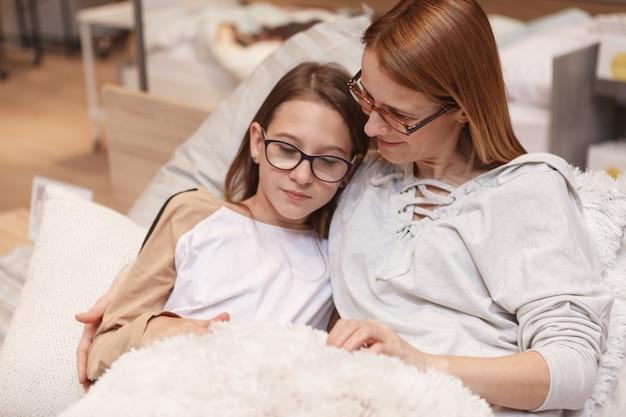 Rijpe vrouw en haar dochter die bij meubelwinkel winkelen