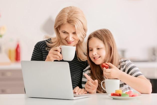 Rijpe vrouw en haar schattige kleindochter met laptop die thuis thee drinkt