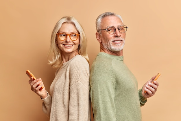 Rijpe vrouw en man staan achter elkaar, hebben plezier samen, gebruiken telefoons om te scrollen sociale netwerken gekleed terloops surfen op internet geïsoleerd over bruine muur