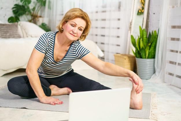 Rijpe vrouw gaat sporten en kijkt naar de monitor online home fitness voor gezondheid het concept van een gezonde levensstijl op volwassen leeftijd