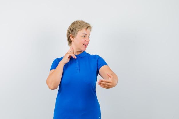 Rijpe vrouw gebaren als make-up in t-shirt