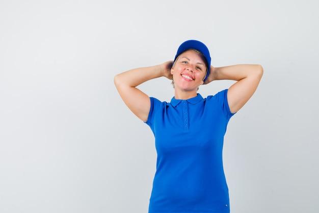 Rijpe vrouw hand in hand achter hoofd in blauw t-shirt en op zoek ontspannen.