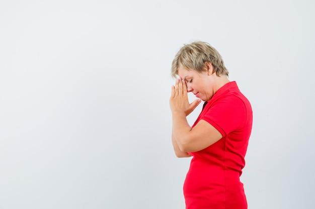 Rijpe vrouw hand in hand biddend gebaar in rood t-shirt en op zoek hoopvol