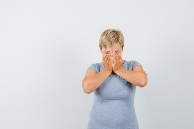 Rijpe vrouw hand in hand op gezicht in grijs t-shirt en op zoek bedroefd