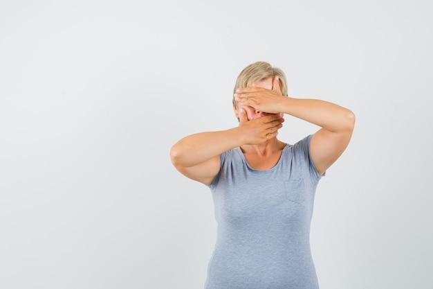 Rijpe vrouw hand in hand op ogen en mond in grijs t-shirt en bang op zoek.