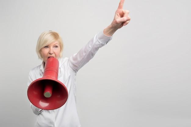 Rijpe vrouw houdt een megafoon dicht bij haar mond en schreeuwt erin. ze verdedigt de mensenrechten.
