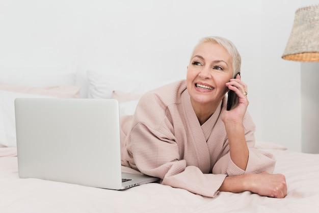 Rijpe vrouw in badjas die op telefoon spreekt en met laptop stelt
