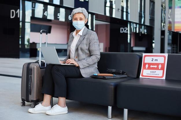 Rijpe vrouw in beschermend masker op zoek zittend in de wachtkamer tijdens pandemie en met behulp van laptopcomputer