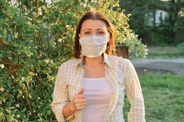 Rijpe vrouw in beschermend medisch masker, openlucht wijfje